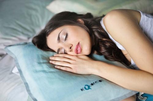 Spánok. Žena spí na posteli.