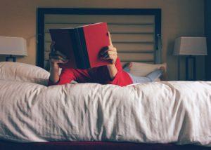 Žena číta knihu v posteli pred spaním