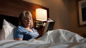 Žena si pred spaním číta knihu v posteli