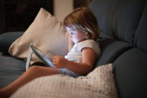 Malé dieťa s notebookom v posteli